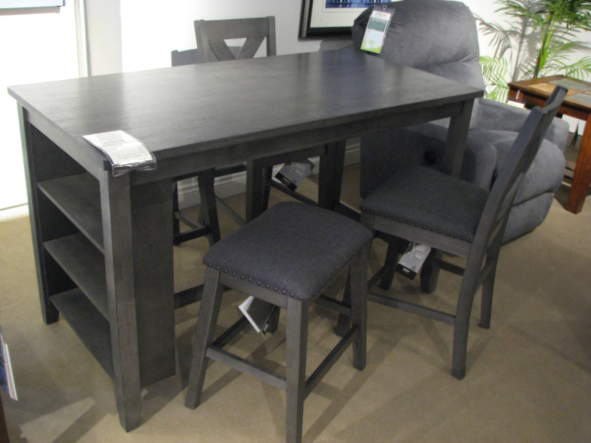 Ashley Pub Dining Table with Three Shelves On One End. Includes Two Stools and Two Chairs
